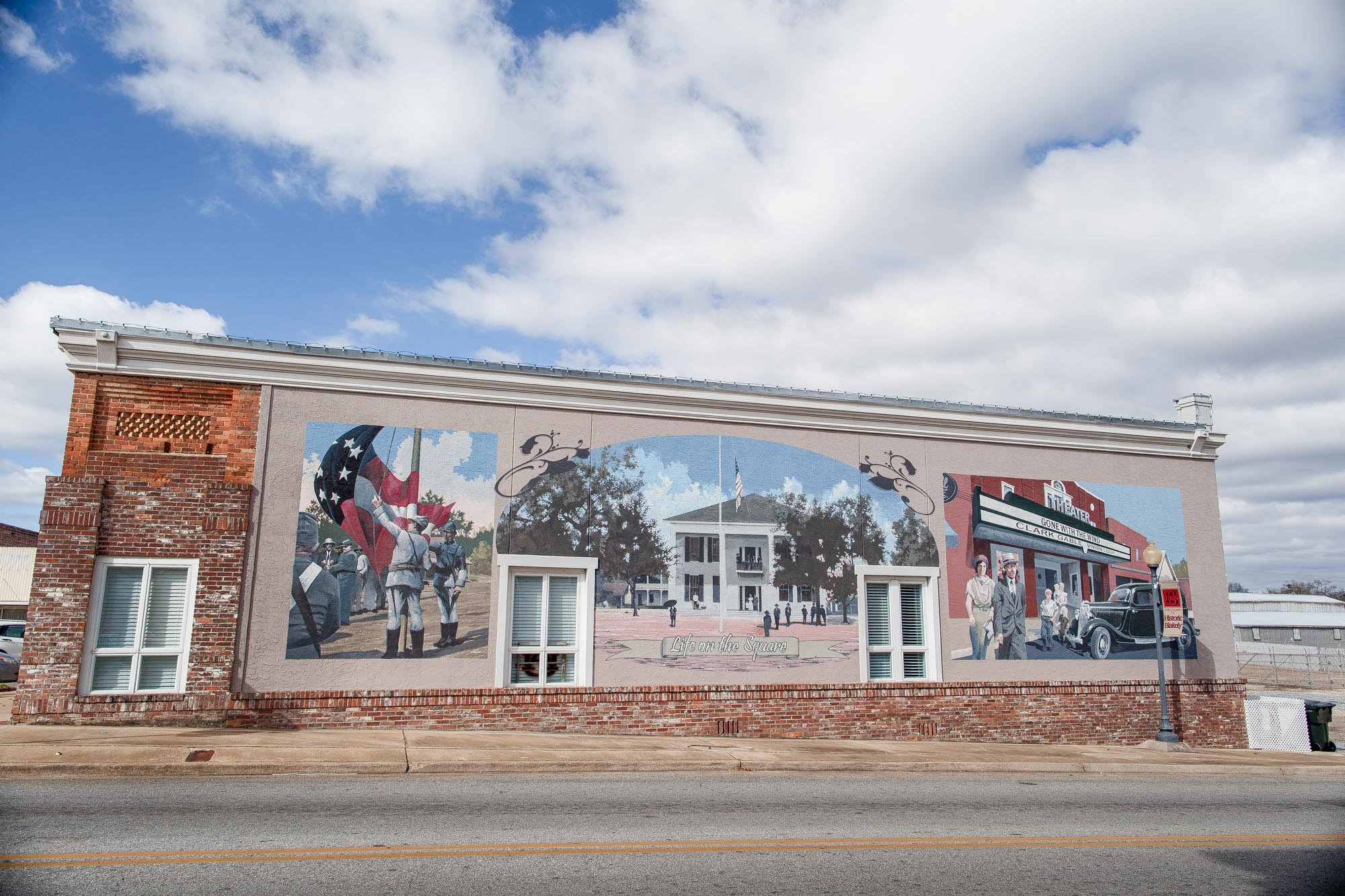 Muralist, Wes Hardin depicts days gone by on the Courthouse Square on the right corner as you approach from the north side of the square.