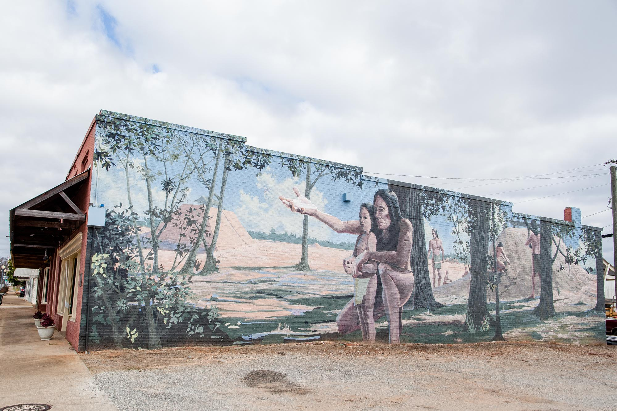 Mural Artist, Wes Hardin, created this very personal view of the native Kolomoki Indians with a prominent father-son relationship. It displays the Kolomoki Mounds in the background. This mural is located on the exterior wall of the Early County Museum.